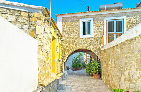 pano: Many old houses in the mountain villages have the arched passes, connecting winding streets, or leading to the yards, Kato Drys, Cyprus.