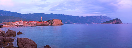romantic places: The seashore of Budva is one of the most romantic places during the twilight, it overlooks the old town - citadel, St Nicholas Island and dark mountains, Montenegro.