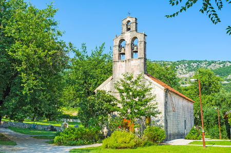 The medieval church of St Petka with the beautiful belfry, surrounded by green garden, Budva, Montenegro. Stock Photo