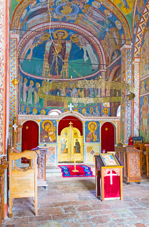 16: BUDVA, MONTENEGRO - JULY 16, 2014: The interior of the Assumption Church of Podmaine Monastery, decorated by frescos and wooden iconostasis, on July 16 in Budva. Editorial