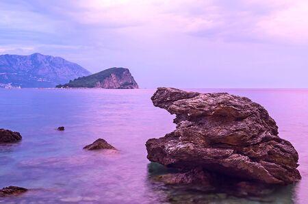The purple seascape from the rocky shore with the Sveti Nikola Island on the background, Budva, Montenegro. Stock Photo