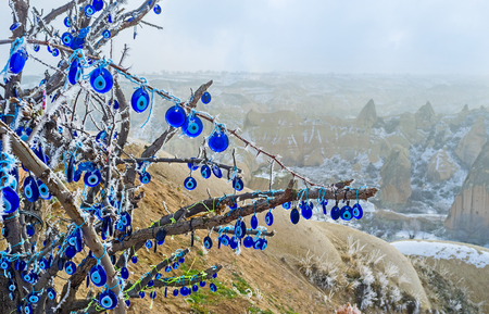 evil eye: The branches of the old tree decorated with the eye-shaped amulets - Nazars, made of blue glass and believed to protect against the evil eye, Cappadocia, Turkey. Stock Photo