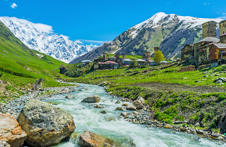 svan: The fast flowing mountain river of Enguri with the medieval Svan towers on its bank and snowy Shkhara Mount on the background, Svaneti, Georgia. Stock Photo
