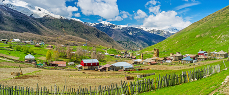 ushguli: The old wooden fence and kitchen garden with old houses and Svan towers on the distance in Zhibiani village of Ushguli comunity, Georgia. Stock Photo