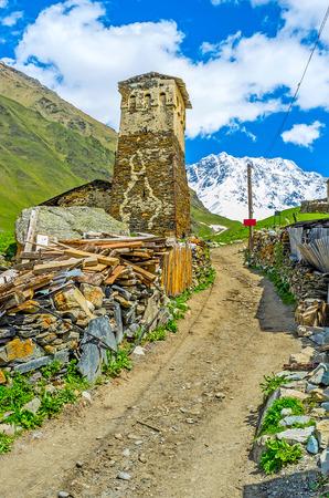 svan: The narrow earthern road in Zhibiani village with the huge medieval Svan Tower, Ushguli comunity, Svaneti, Georgia.
