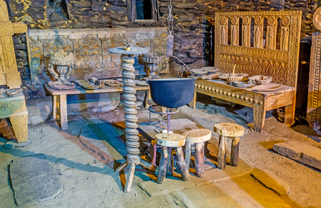 ethnographic: USHGULI, GEORGIA - MAY 22, 2016: The carved wooden benches and chairs, stands around the cauldron for cooking over an open fire in Ethnographic Museum in the medieval house of Svan family, on May 22 in Ushguli.
