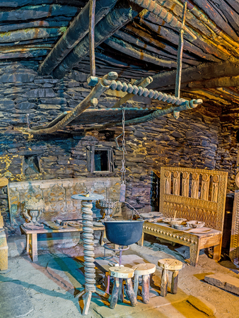 svan: USHGULI, GEORGIA - MAY 22, 2016: The old cauldron for cooking over an open fire in Ethnographic Museum in the medieval house of Svan family, on May 22 in Ushguli. Editorial