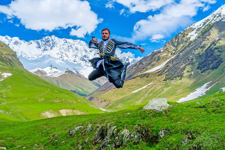 ushguli: USHGULI, GEORGIA - MAY 22, 2016: The  jump from the ethnic war dance in the national costume in Enguri gorge, at the foot of Shkhara Mount, on May 22 in Ushguli. Editorial