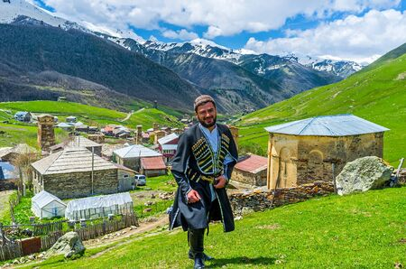 ushguli: USHGULI, GEORGIA - MAY 22, 2016: The  young Svan in traditional costume poses with the village on the background, on May 22 in Ushguli. Editorial
