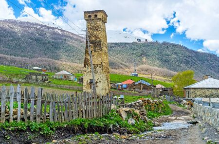 ushguli: The medieval Svan tower stands in the kitchen garden and surrounded by the snowbound mountain range, Ushguli, Georgia.