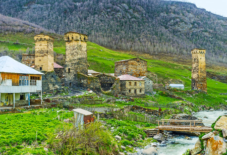 The old Svan towers and small tilted houses on the bank of Enguri river in Ushguli community, Upper Svaneti, Georgia.