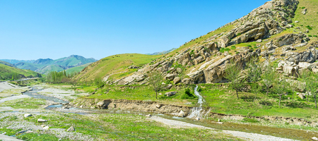 The narrow twisted river flows along the rocky valley between Zarafshan and Gissar mountain ranges of Pamir-Alay, the cows graze on the hills, Uzbekistan.