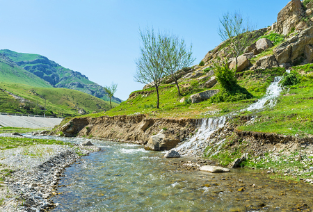 The small stream meets the mountain river in valley between Zarafshan and Gissar mountain ranges of Pamir-Alay, Uzbekistan.