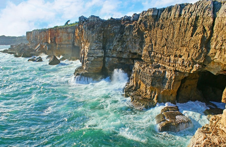 jaws: Panorama of the rocky coast with the black grotto, named the Jaws of the Devil (Boca do Inferno) or the Devils Cave, Cascais, Portugal. Stock Photo