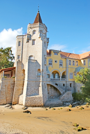 The medieval stone tower of Palace of Condes de Castro Guimaraes, located on the sand shore of a small bay, Cascais, Portugal. Editorial