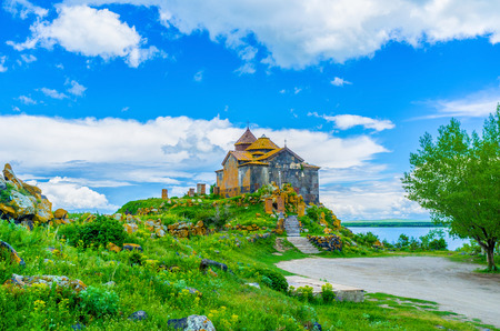 The stone church of Hayravank Monastery covered with bright orange lichen, located on the gentle hill on the bank of Sevan Lake, Armenia. Stock Photo