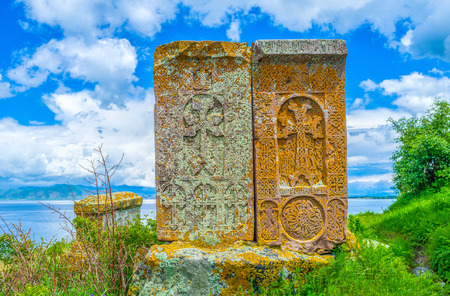 Two medieval tombstones named in Armenia the khachkars among the greenery on the bank of Sevan Lake, Hayravank, Armenia. Stock Photo