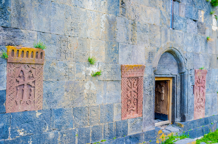 frontage: The frontage wall of Hayravank Monastery decorated with the red khachkars, built in it, Armenia.