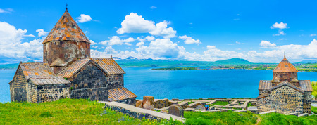 Panorama of the churches of Sevanavank Monastery, with the medieval cemetery between them and the wide Sevan Lake on the background, Armenia. Stock Photo - 62285662