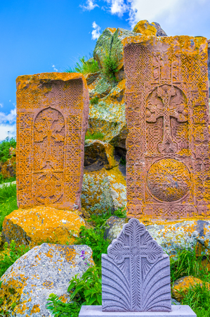 The medieval red khachkars, made of local travertine stone with the complex carved patterns, covered with yellow and orange lichen, Hayravank, Armenia.