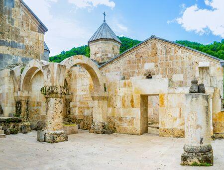 The view from gavit (frontage hall) of St Astvatsatsin Church on the stone wall and dome of St Grigor Church, Haghartsin Monastery, Armenia.