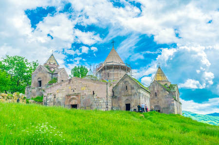 gosh: GOSH, ARMENIA - MAY 31, 2016: The green foothill is topped with the Goshavank Monastery famous gor its beautiful churches and medieval khachkars, on May 31 in Gosh.