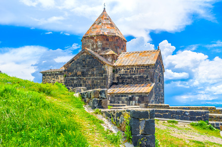 The black church of the Holy Apostles on the green slope of the hill of Sevan Peninsula, Sevan, Armenia. Stock Photo
