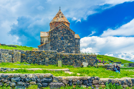 SEVAN, ARMENIA - MAY 31, 2016: The old Church of Holy Apostles of Sevanavank Monastery surrounded by stone fence, on May 31 in Sevan Editorial