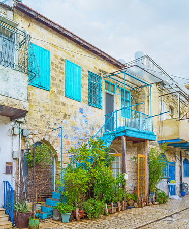 The stone cottage decorated with bright blue shutters and many plants in pots, Safed, Israel. Editorial