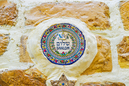 kabbalah: SAFED, ISRAEL - FEBRUARY 22, 2016: The house wall decorated with the circle porcelain tile, with the peace dove and colorful floral pattern, on February 22 in Safed.