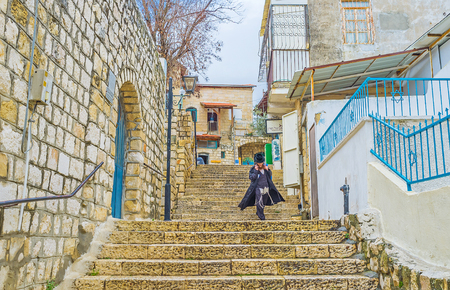 SAFED, ISRAEL - FEBRUARY 22, 2016: The young Orthodox Hasid goes down the stairs in the old town, on February 22 in Safed.