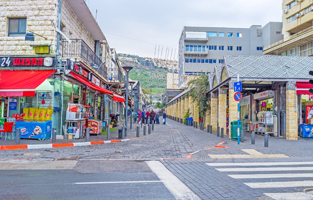residential street: TIBERIAS, ISRAEL - FEBRUARY 22, 2016: The residential street with numerous stores and supermarkets, offering the wide range of goods, on February 22 in Tiberias, Israel. Editorial