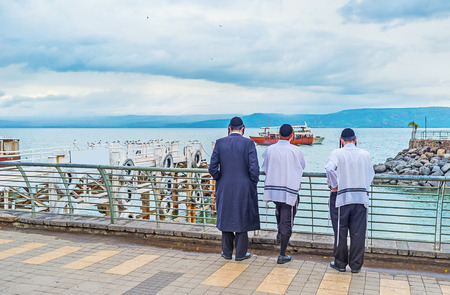Three young Orthodox Hasid friends in traditional skullcaps and tallits stand on embankment of the Sea of Galilee and enjoy the view, Tiberias, Israel.