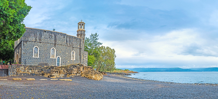 primacy: The black pebble beach at the Sea of Galilee is the best place to relax, enjoy the natures beauty and the Church of the Primacy of St Peter, Tabgha, Isael.