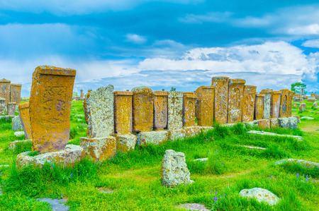 The row of old khachkars, ruined by weathering and covered with lichen and moss stands on the green meadow of Noratus Cemetery, Gegharkunik Province, Armenia.