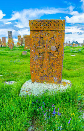 The orange khachkar of tuff, covered with lichen and located at the Noratus Cemetery, Gegharkunik Province, Armenia.