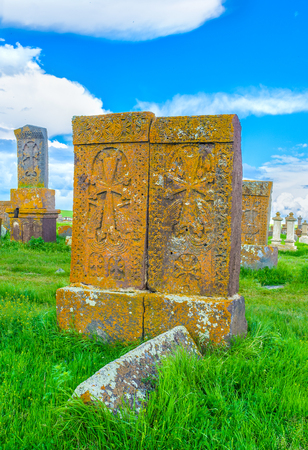The couple of medieval khachkars, standing close to each other, covered with complex patterns and located at Noratus Cemetery, Gegharkunik Province, Armenia. Stock Photo