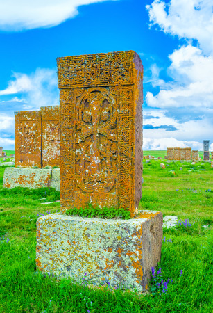 The colorful lichen makes old khachkars picturesque, it covers the stone blocks and provide them with bright colors, Noratus Cemetery, Gegharkunik Province, Armenia.