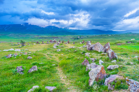 The long alley leads to the circles of ancient stones of Zorats Karer archaeological site, Sisian, Syunik Province, Armenia. Stock Photo