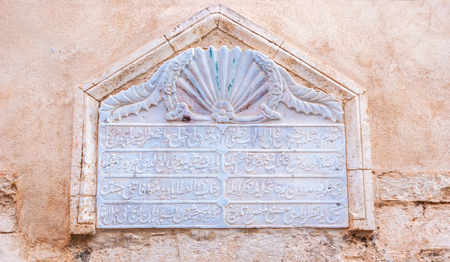 rethymno: RETHYMNO, GREECE - OCTOBER 16, 2013: The old arabic inscription, carved on the marble block, is built in the houses wall, on October 16 in Rethymno.