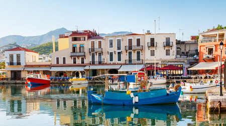 The colorfull fishing boats are moored in the old port, adjacent to the tiny cafes and taverns, Rethymno, Crete, Greece.