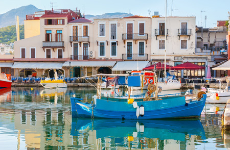 The old harbor is surrounded by the small cottages, occupied with the best fish and sea food cafes and taverns, Rethymno, Crete, Greece. Stock Photo