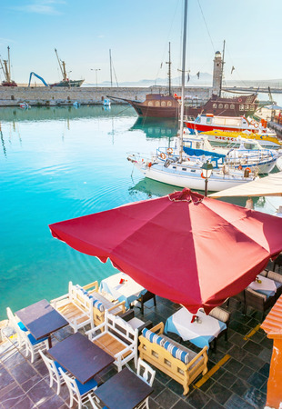 RETHYMNO, GREECE - OCTOBER 16, 2013: The taverns of the old harbor protect the outdoor terraces with the sunshades, hiding the tables and chairs from the sun, on October 16 in Rethymno. Editorial
