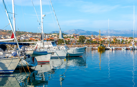 The white yachts reflect in calm waters in the new port, Rethymno, Crete, Greece.