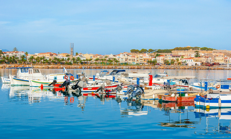 fortezza: The colorful motor boats along the shipyard with the old town and medieval Fortezza citadel on the background, Rethymno, Crete, Greece.