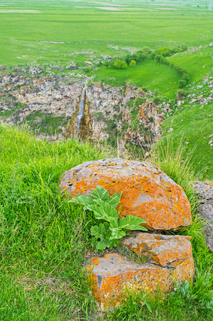 The amazing nature of the mountain village of Saro with the view on the waterfall behind the bright orange stone, covered with lichen, Georgia.