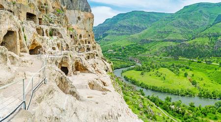 monastic: The narrow tourist way at the edge of precipice in Vardzia complex of carved in rock monastic caves, Samtskhe-Javakheti Region, Georgia. Stock Photo