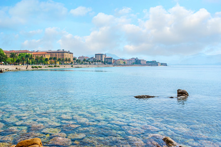expose: The pure waters expose the rocky seabed at the Ajaccio coast with the old town buildings on the background, Corsica, France.