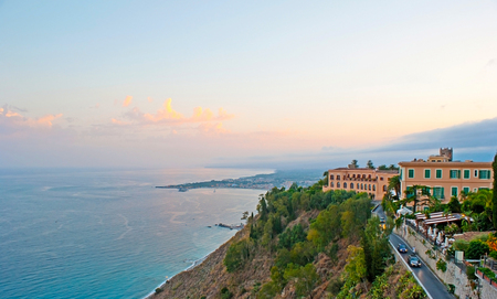 The sunset over Ionian Sea coast from the slopes of Taormina with Giardini Naxos resort on the background, Sicily, Italy.