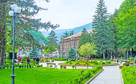 pleasent: BORJOMI, GEORGIA - MAY 26, 2016: The pleasent Mineral Water Park with narrow pathes, flower beds, lush greenery and famous hot water source, on May 26 in Borjomi.